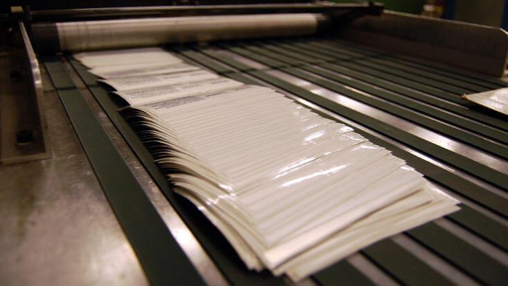 Etiketter blir kappet til ark i Cartes-kappemaskin, på Ellco Etikett.