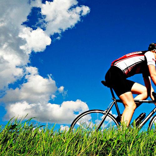 Syklist som sykler i fullt utstyr, blå himmel og grønt gress.